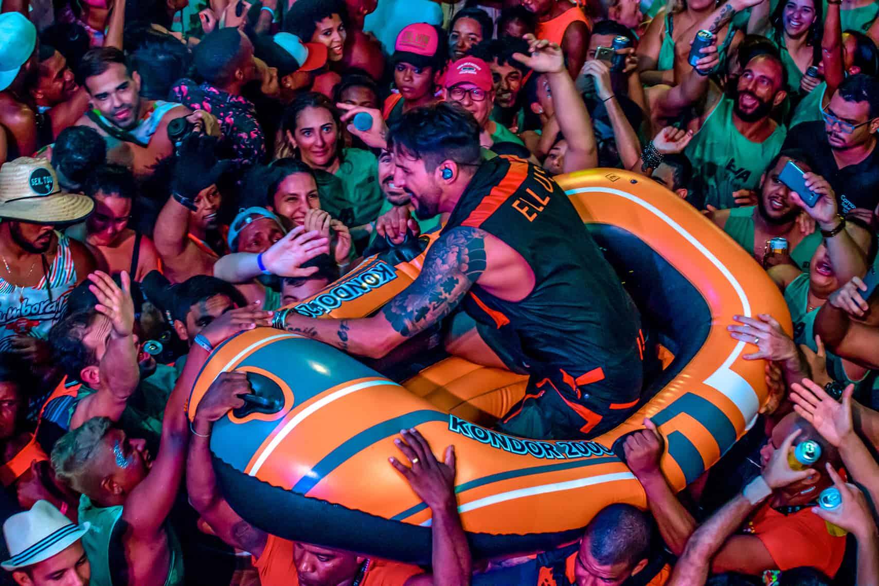 Foto do cantor Felipe Pezzoni cantando em cima de um bote inflável carregado pelos foliões do bloco EVA