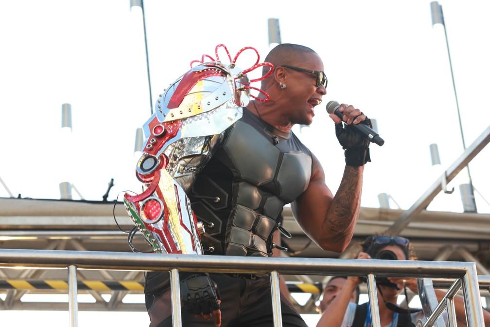 Foto do cantor Léo Santana em cima do trio elétrico do seu bloco no carnaval de Salvador, fantasiado de homem do futuro utilizando um braço mecânico