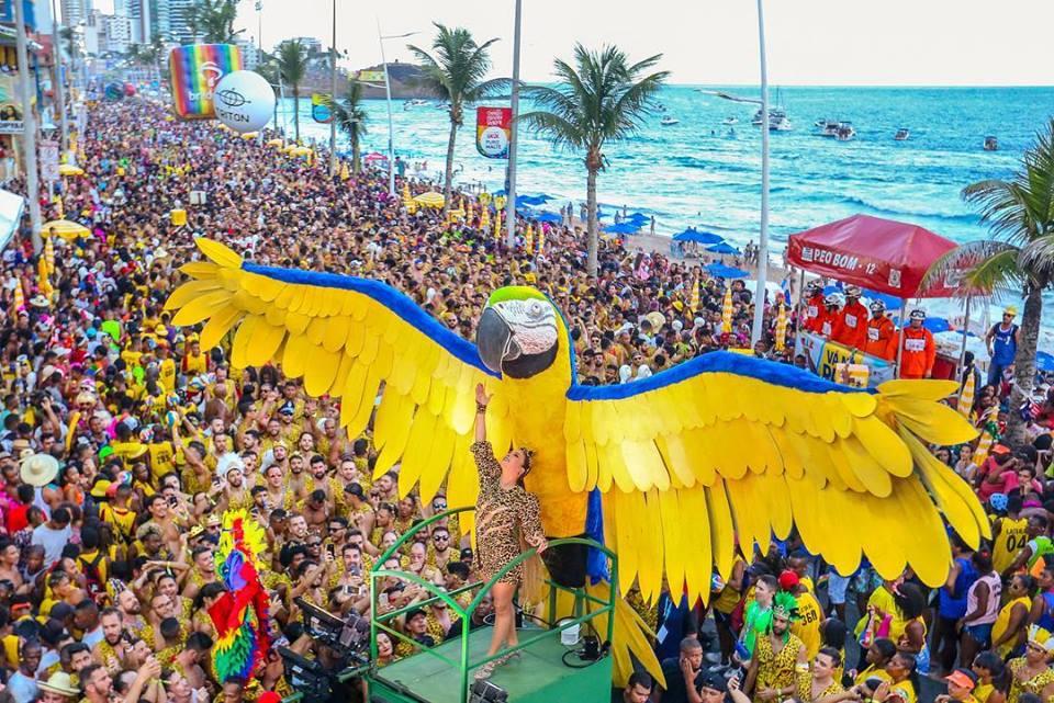 Foto da cantora Claudia Leitte vestida de onça em frente a uma grande Arara amarela ornamentada no seu trio do Carnaval de Salvador