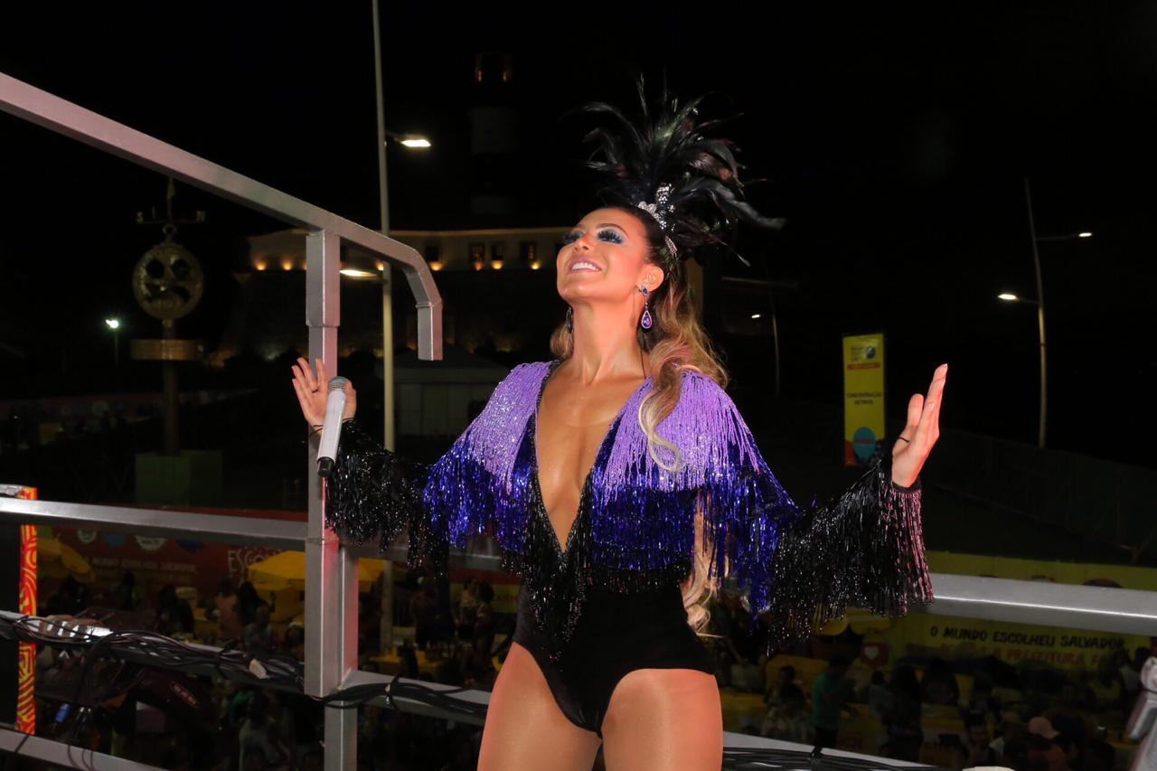 Foto com a cantora Vina Calmon, da banda Cheiro de amor em cima do trio elétrico com uma roupa preta e roxa com brilhos