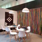 Foto da loja temporária do Folia Bahia no shopping Paralela com cadeiras brancas ao redor de uma mesa e uma cortina de faixas do Senhor do Bonfim por trás.