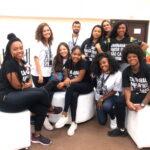 Foto de parte da equipe de atendimento da entrega do Folia Bahia com 10 pessoas sorrindo vestidas com camisas pretas e brancas