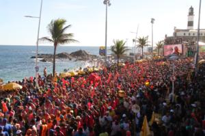 Foto do circuito Barra Ondina com foliões em frente ao trio elétrico na orla da Barra com o Farol ao fundo
