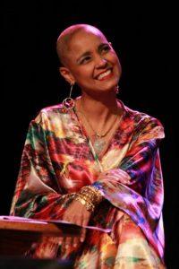Cantora Carla Visi sentada em uma cadeira e sorrindo