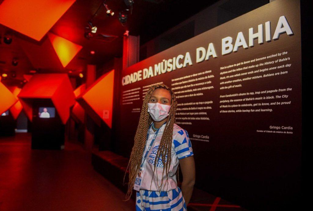 foto de mulher em frente a um painel escrito museu cidade da música da bahia